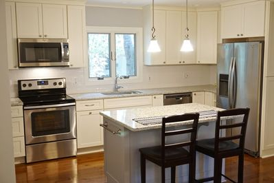 Beautiful and bright renovated kitchen with granite countertops and an island
