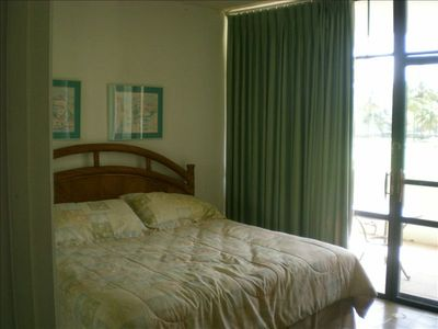 King bed in master bedroom, adjoining balcony with view in background.