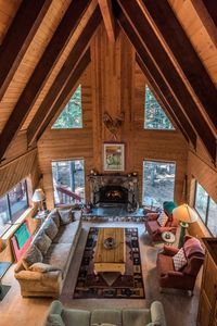 Cozy great room, wood burning fireplace for family time under cathedral ceiling