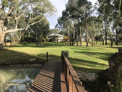 View of the house from the jetty showing the front lawns and neighbours