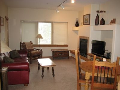 Living room with fireplace, flat screen TV, DVD player; door to balcony