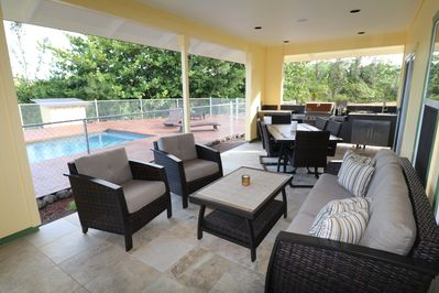 Large covered lanai with outdoor kitchen and dining - lap pool in the background