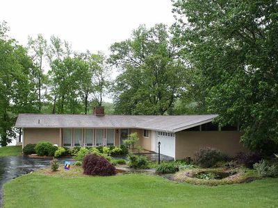 Photo for Cozy lake front home with gentle slope to covered dock and screened in porch.