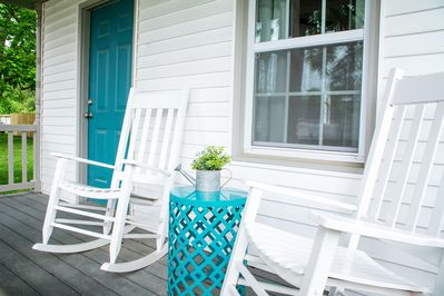 White rocking chairs to watch the bicyclists and locals ride by