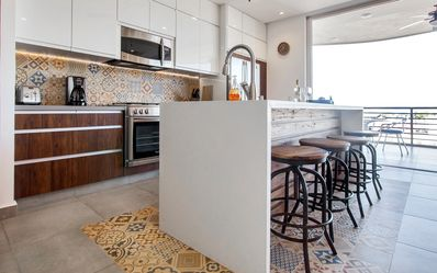 Modern Kitchen with quartz waterfall island that is open to the living space.
