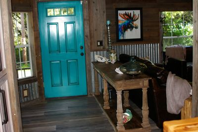 The bold teal door bids you to come in & discover what lies within