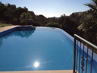 Large infinity pool with sunbathing area to 3 side