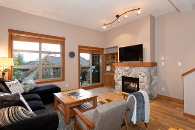 Bright living area with gas fireplace and TV