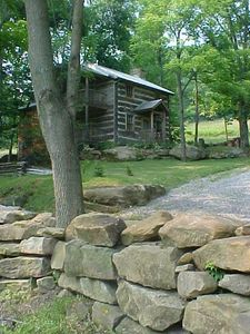 Stone wall and log house.
