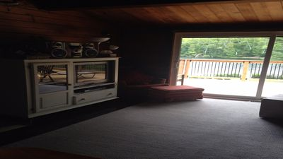 Living room with screened door walk out to raised deck.