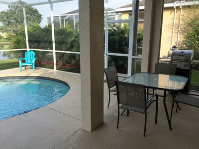 outdoor grill and patio area with table and four chairs.additional 6 chairs ava