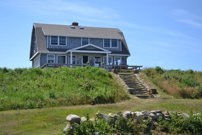Ocean side view of house with deck and steps to path to private beach