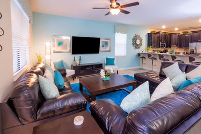Wall mounted HDTV in living room with plenty of comfortable leather seating