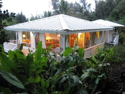 Beautiful home surrounded by lush greenery and lanai with ocean view.