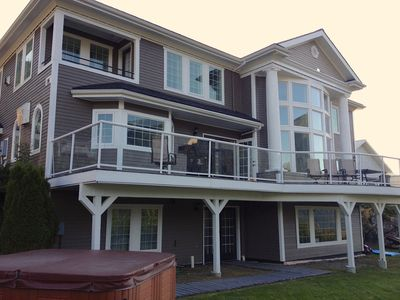 View side of three story home with large deck, window wall & walk out hot tub.