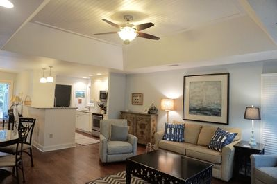 Comfortable living room with raised ceiling that opens up to renovated kitchen