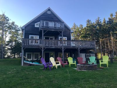 Back of cottage with huge wrap around deck and private deck off upper floor bedroom.