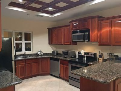 Gourmet kitchen features granite and stainless steel  Cuisinart appliances.