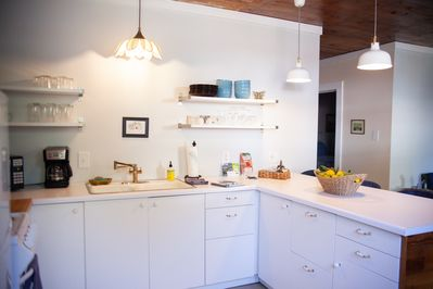 Kitchen has open shelving for dishes and plenty of counter and cabinet space