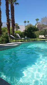 Sparkling pool and yard with mountain views, dining, seating and lounge areas