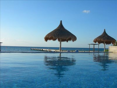 Swim in the infinity pool with the private pier and the Mexican Caribbean beyond