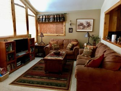 The cozy living room has seating for six with soft microsuede sofas.