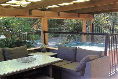 main deck area with seating and hot tub