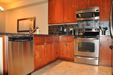 Kitchen with gourmet appliances and slab granite countertop
