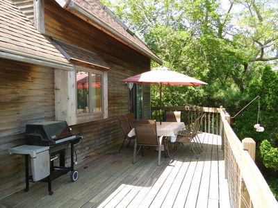 Deck with grill and dining table, overlooking back yard