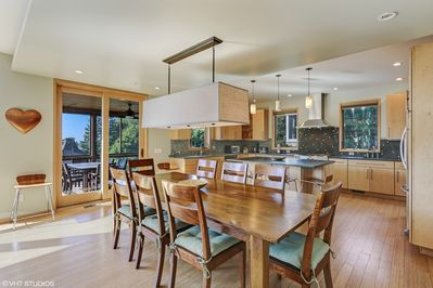 Open floor plan dining room adjacent to kitchen island and screened in porch