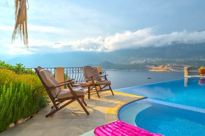 Swimming pool, sea and mountain view with chairs