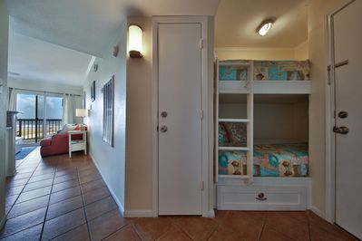 Twin bunk beds in hall across from bath.