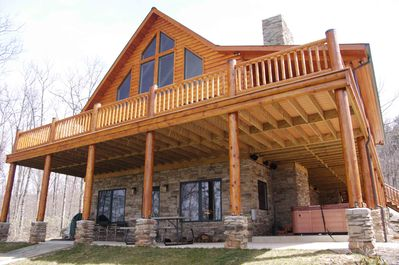 Front of cabin w/ upper wrap around deck and lower walk out basement w/ hot tub