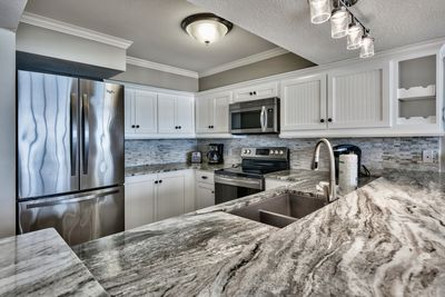 Granite counters with all stainless appliances and white cabinetry