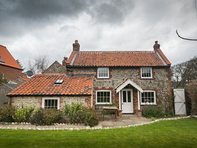 Photo for Charming detached flint cottage on village green, 5 minute stroll to beach
