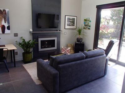 Living room with gas fireplace, sleeper sofa and   large flat screen TV.