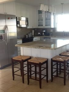Modern white kitchen with stainless steel appliances, and exit to the back deck