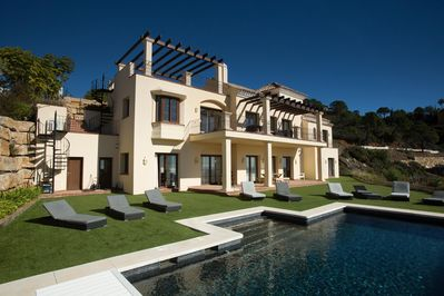 The villa, pool and sun loungers
