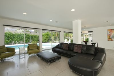Living area with wall of glass leading to the outdoor pool area