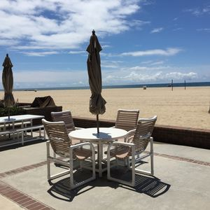 New patio chairs and umbrellas on large patio fronting the beach!