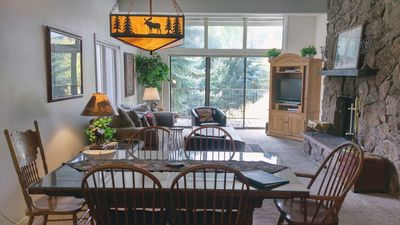 Living room with wood fireplace, dining table, and  balcony with gas BBQ