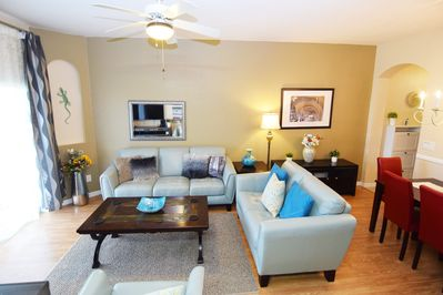 Stylish lounge with leather sofas, TV, sliding doors to the patio, dining area