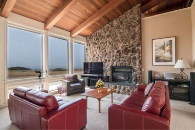 Living room with fireplace, TV, expansive views.