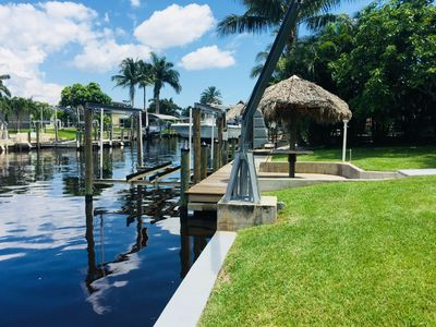 Modern tropical swimming pool home on salt water canal with tiki hut & boat  dock - Yacht Club
