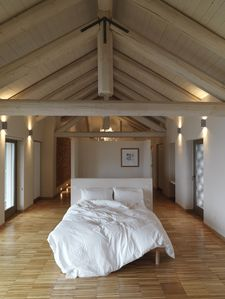 Master bedroom with kingsize bed, oak parquet floor, barn style wooden ceiling