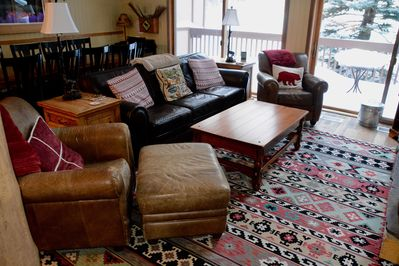 Comfortable leather chairs and couch in front of fireplace