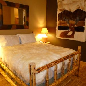 Queen size bed with New Zealand sheep skin cover