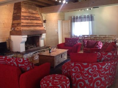 Chalet lounge for 10 people around the log fire with dining table in background.
