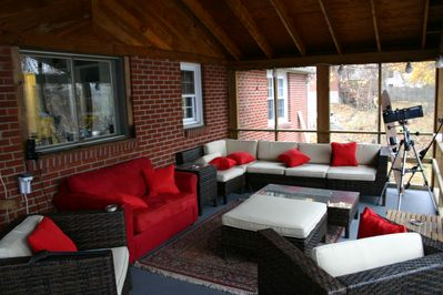 Screened-in-porch. Serving bar not pictured. Red couch is a twin pull-out bed.