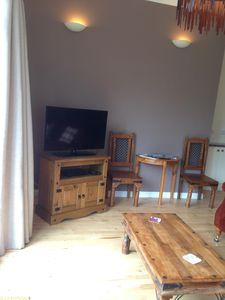 Open plan living area with flat screen tv and woodburner